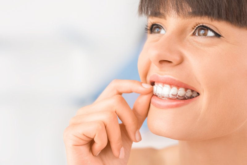 woman inserting Invisalign trays smiling